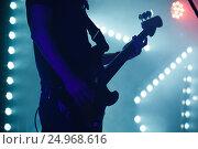 Купить «Bass guitar player in blue stage lights», фото № 24968616, снято 11 декабря 2016 г. (c) EugeneSergeev / Фотобанк Лори