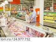 Купить «couple with shopping cart buying meat at grocery», фото № 24977732, снято 21 октября 2016 г. (c) Syda Productions / Фотобанк Лори