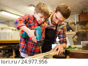 Купить «father and son with drill working at workshop», фото № 24977956, снято 14 мая 2016 г. (c) Syda Productions / Фотобанк Лори