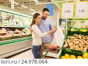 Купить «happy couple weighing tomatoes on scale at grocery», фото № 24978064, снято 21 октября 2016 г. (c) Syda Productions / Фотобанк Лори