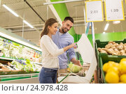 Купить «happy couple weighing cabbage on scale at grocery», фото № 24978428, снято 21 октября 2016 г. (c) Syda Productions / Фотобанк Лори