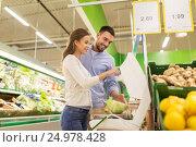 Купить «happy couple weighing cabbage on scale at grocery», фото № 24978428, снято 21 октября 2016 г. (c) Syda Productions / Фотобанк Лори