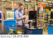 Купить «couple buying food at grocery at cash register», фото № 24978440, снято 21 октября 2016 г. (c) Syda Productions / Фотобанк Лори