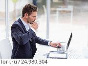 Купить «Businessman using laptop at desk and drinking coffee», фото № 24980304, снято 3 ноября 2016 г. (c) Wavebreak Media / Фотобанк Лори