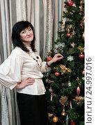 Купить «Счастливая женщина стоит возле новогодней ёлки», эксклюзивное фото № 24997016, снято 31 декабря 2016 г. (c) Игорь Низов / Фотобанк Лори