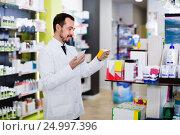 Купить «Male pharmacist looking for right medicine», фото № 24997396, снято 14 декабря 2016 г. (c) Яков Филимонов / Фотобанк Лори