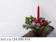 Купить «Christmas background with red candle and ornaments centerpiece», фото № 24998416, снято 27 ноября 2016 г. (c) TasiPas / Фотобанк Лори