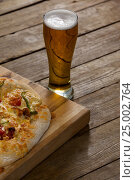 Купить «Delicious pizza served on wooden board with a glass of beer», фото № 25002764, снято 30 сентября 2016 г. (c) Wavebreak Media / Фотобанк Лори