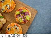 Купить «Various pizza arranged on a wooden tray», фото № 25004536, снято 30 сентября 2016 г. (c) Wavebreak Media / Фотобанк Лори