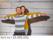 Купить «Composite image of young couple standing with arms outstretched», фото № 25005692, снято 25 марта 2019 г. (c) Wavebreak Media / Фотобанк Лори