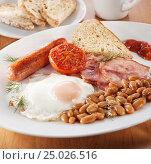 Традиционный английский завтрак:бекон, яичница, колбаски, бобы,помидор, гренки в белой тарелке на столе. Стоковое фото, фотограф Анастасия Богатова / Фотобанк Лори