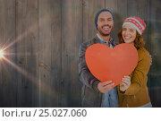 Купить «Composite image of happy young couple holding heart shape paper», фото № 25027060, снято 11 декабря 2019 г. (c) Wavebreak Media / Фотобанк Лори