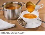 Cream of pumpkin from the pan ladle is poured into a bowl. Стоковое фото, фотограф Анастасия Богатова / Фотобанк Лори