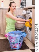 Купить «Young wife woman washing clothes near machine», фото № 25042344, снято 27 сентября 2016 г. (c) Elnur / Фотобанк Лори