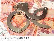 Наручники и деньги. Стоковое фото, фотограф Всеволод Карулин / Фотобанк Лори