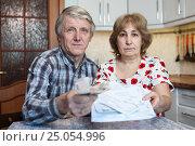 Купить «Мужчина и женщина пенсионного возраста протягивают квитанции и деньги в руках, сидя за столом на кухне», фото № 25054996, снято 6 ноября 2016 г. (c) Кекяляйнен Андрей / Фотобанк Лори