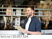 Купить «man with clipboard and milking cows on dairy farm», фото № 25057524, снято 12 августа 2016 г. (c) Syda Productions / Фотобанк Лори