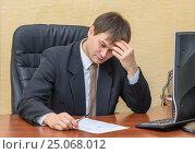 Купить «Мужчина в офисе задумавшись смотрит в документ», фото № 25068012, снято 5 февраля 2017 г. (c) Гетманец Инна / Фотобанк Лори