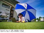 Купить «Woman on the grass, looking at the laptop under umbrella near the campe.», фото № 25068132, снято 27 июня 2016 г. (c) Андрей Армягов / Фотобанк Лори