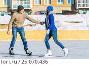 Купить «Young couple riding on a skating rink background colored», фото № 25070436, снято 29 января 2017 г. (c) Zakirov Aleksey / Фотобанк Лори