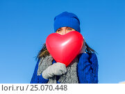 Купить «Girl looks covering face balloon in the shape of heart», фото № 25070448, снято 29 января 2017 г. (c) Zakirov Aleksey / Фотобанк Лори