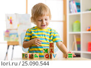Little preschooler child boy playing with toy cubes and memorizing letters. Early education concept. Стоковое фото, фотограф Оксана Кузьмина / Фотобанк Лори