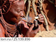 Купить «Himba woman lighting and smoking her pipe, Marienfluss Valley, Kaokoland Desert, Namibia. October 2015», фото № 25139896, снято 2 июля 2020 г. (c) Nature Picture Library / Фотобанк Лори