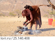 Купить «Himba woman cooking maize flour open fireplace, Marienfluss Valley, Kaokoland Desert, Namibia. October 2015», фото № 25140408, снято 26 мая 2019 г. (c) Nature Picture Library / Фотобанк Лори