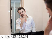 Man take care about his skin. Cheerful beaded guy caring of his skin. Handsome man look in mirror in bathroom in early morning. Handsome man care about skin. Стоковое фото, фотограф Довженко Анастасия / Фотобанк Лори