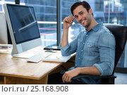 Купить «Happy man sitting at desk in office», фото № 25168908, снято 16 октября 2016 г. (c) Wavebreak Media / Фотобанк Лори