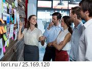 Купить «Business executives discussing over sticky notes», фото № 25169120, снято 16 октября 2016 г. (c) Wavebreak Media / Фотобанк Лори