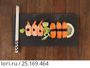 Купить «Nigiri sushi served with chopsticks in black stone slate», фото № 25169464, снято 8 декабря 2016 г. (c) Wavebreak Media / Фотобанк Лори
