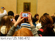 Tourists crowding round the Mona Lisa by Leonardo DaVinchi and taking photographs on cameras and phones,  the Louvre, Paris, France, November 2013. Редакционное фото, фотограф Staffan Widstrand / Nature Picture Library / Фотобанк Лори