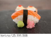 Купить «Nigiri and uramaki sushi served on black stone slate on wooden table», фото № 25191508, снято 8 декабря 2016 г. (c) Wavebreak Media / Фотобанк Лори