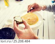 Купить «close up of hands applying butter to bread», фото № 25208484, снято 20 сентября 2015 г. (c) Syda Productions / Фотобанк Лори
