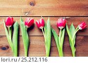 Купить «close up of red tulip flowers on wooden table», фото № 25212116, снято 28 января 2016 г. (c) Syda Productions / Фотобанк Лори