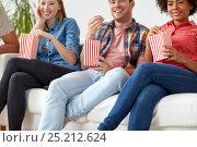 Купить «close up of happy friends eating popcorn at home», фото № 25212624, снято 14 августа 2016 г. (c) Syda Productions / Фотобанк Лори