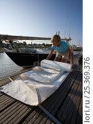 Купить «Woman folding sails of a Contessa 26 on the pontoon in Pauillac, France, September 2009. Model released.», фото № 25369376, снято 21 июля 2018 г. (c) Nature Picture Library / Фотобанк Лори
