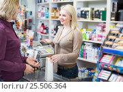 Купить «Mature customer paying for purchases», фото № 25506364, снято 26 апреля 2018 г. (c) Яков Филимонов / Фотобанк Лори