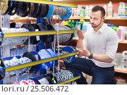 Купить «Man next to showcase with metallic chains», фото № 25506472, снято 20 февраля 2019 г. (c) Яков Филимонов / Фотобанк Лори