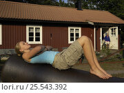 Lisa Widstrand, sunbathing on an old cannon, Gotska Sandön National Park, Sweden, July 2007. Model released. Стоковое фото, фотограф Staffan Widstrand / Nature Picture Library / Фотобанк Лори