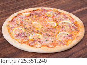 Hot pizza slice with melting cheese on a rustic wooden table. Стоковое фото, фотограф Aleksandr Ryzhov / Фотобанк Лори