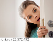 Купить «scared beautiful girl hiding behind door at home», фото № 25572492, снято 5 ноября 2016 г. (c) Syda Productions / Фотобанк Лори