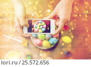 Купить «close up of hands with easter eggs and smartphone», фото № 25572656, снято 27 января 2016 г. (c) Syda Productions / Фотобанк Лори