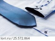 Купить «close up of shirt and blue patterned tie», фото № 25572864, снято 15 сентября 2016 г. (c) Syda Productions / Фотобанк Лори