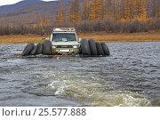 Переправа через реку на автомобильных камерах внедорожника с помощью моторной лодки (2016 год). Редакционное фото, фотограф Александр Игнатов / Фотобанк Лори