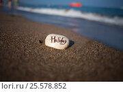 Начало отпуска, камешек расписанный ручкой с фразой Holiday. Стоковое фото, фотограф Elena Kucherenko / Фотобанк Лори