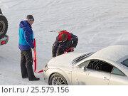 Двое мужчин прицепляют буксировочный трос к застрявшей легковой машине (2017 год). Редакционное фото, фотограф Юлия Юриева / Фотобанк Лори