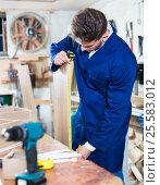 Купить «Male worker checking measurements», фото № 25583012, снято 7 ноября 2016 г. (c) Яков Филимонов / Фотобанк Лори