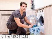 Купить «Young husband man doing laundry at home», фото № 25591212, снято 10 октября 2016 г. (c) Elnur / Фотобанк Лори